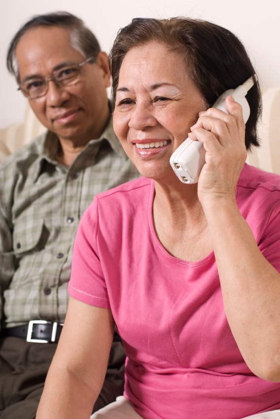 Picture of an Asian woman on the phone with an Asian man looking on