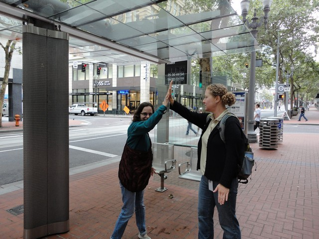 Travel trainer from RideWise and student, pictured at bus stop, share a congratulatory high-five
