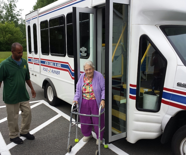 Older adult with walker stepping off of bus