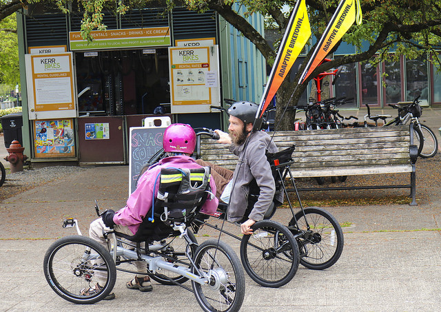 Two riders on adaptive bicycles speak with each other