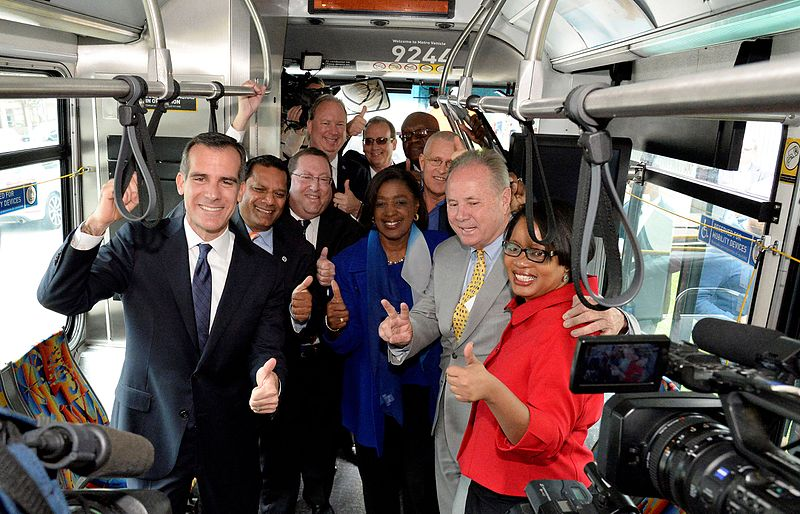A group of officials poses for a photo inside a bus