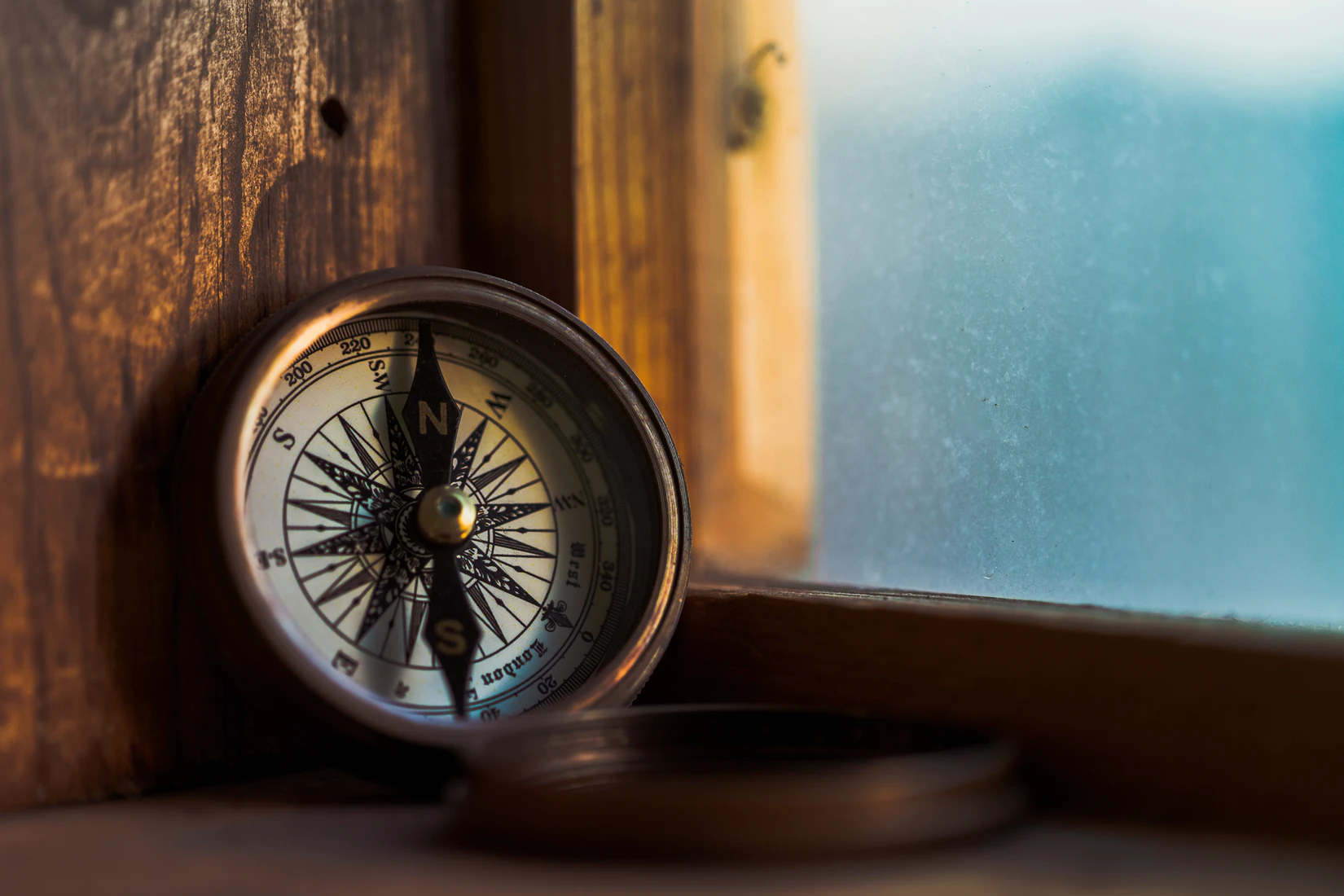 A compass sits on a windowsill overlooking the sea.