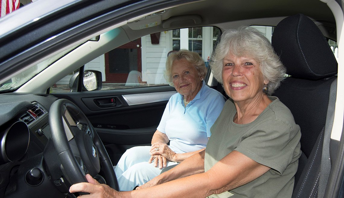 Two smiling older women in the front seats of a car.