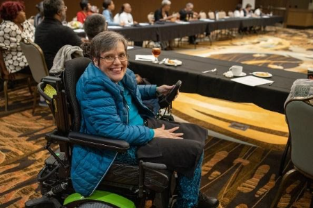 A woman in a wheelchair smiles at the camera, while sitting at a large table during a meeting.