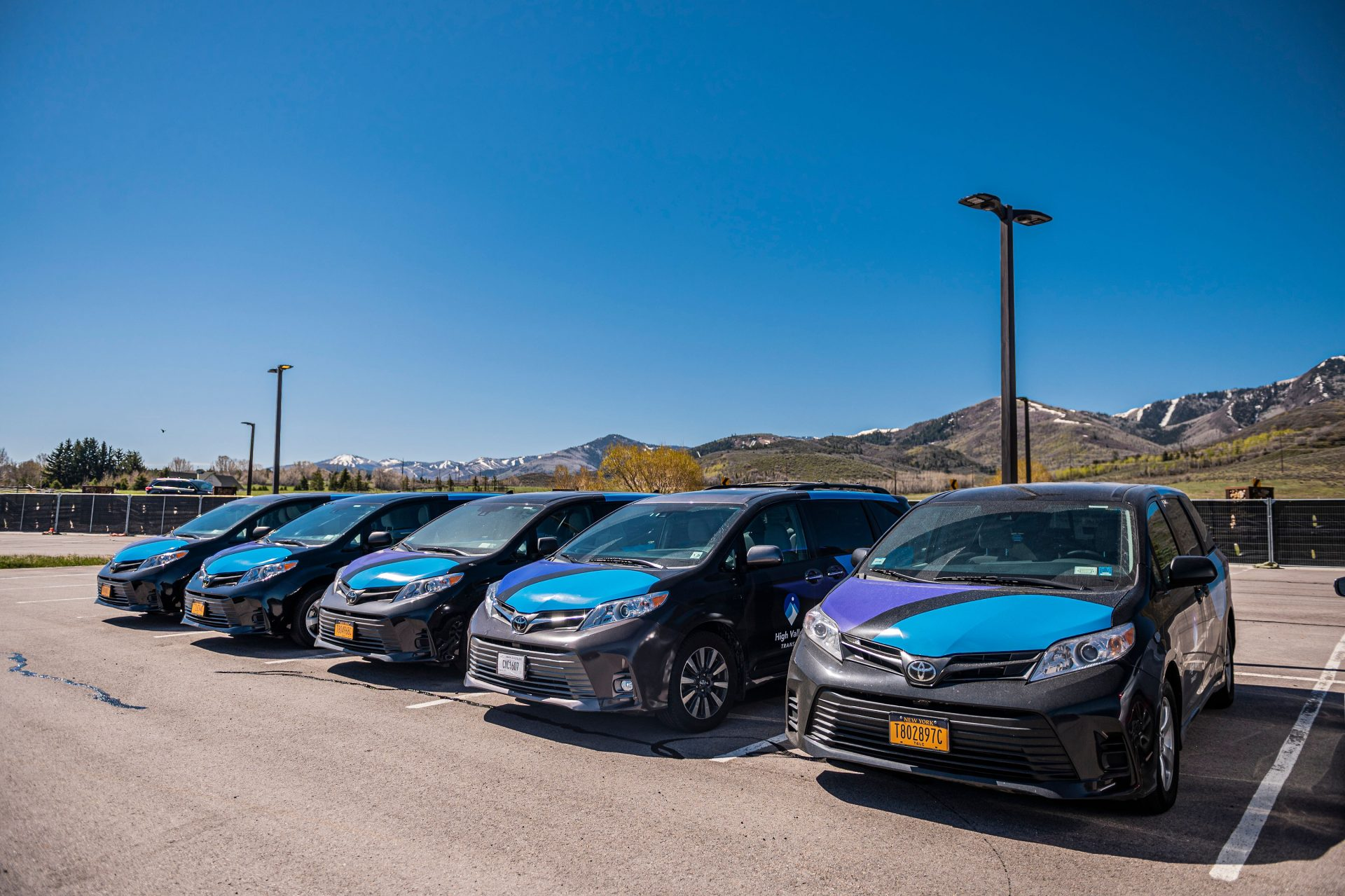 Five Micro vehicles parked in a parking lot on a sunny day, mountains are in the background