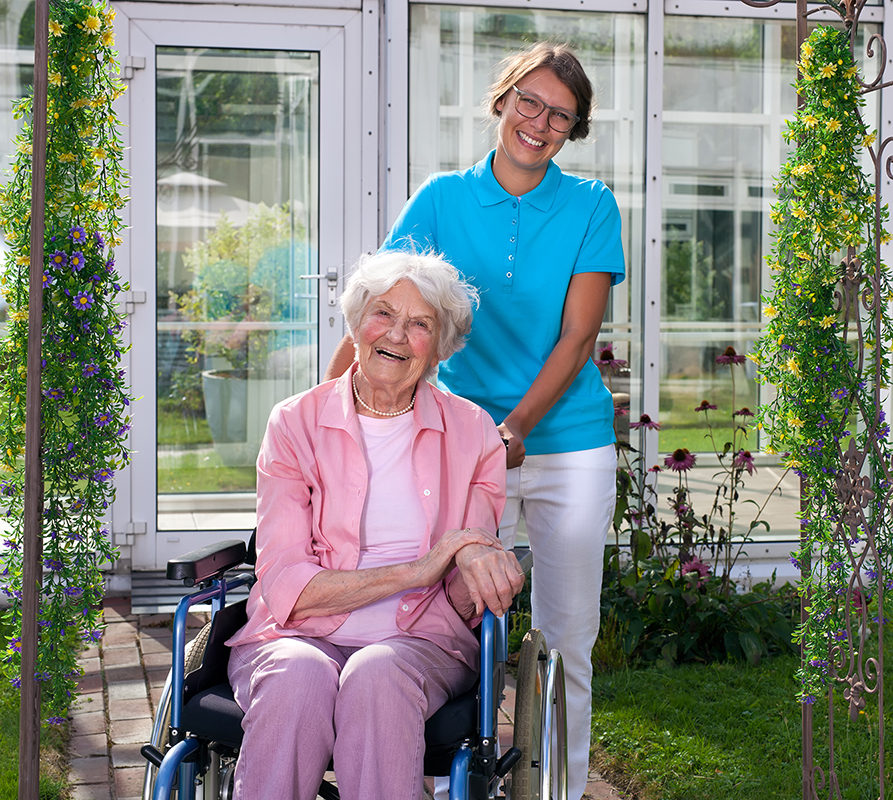 Female professional carer or middle-aged daughter behind happy elderly woman in wheelchair in a green garden.
